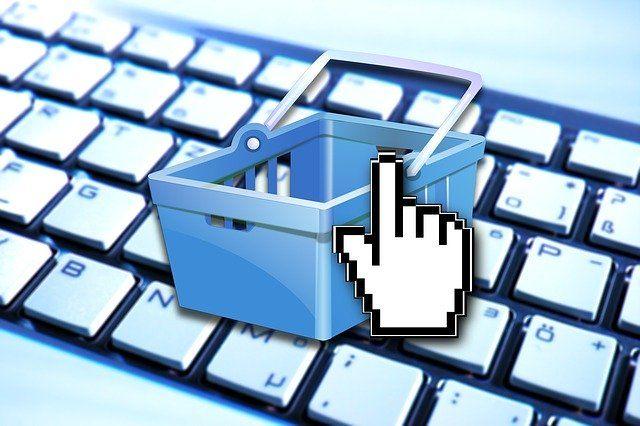 Mauszeiger auf digitalem Warenkorb mit Tastatur im Hintergrund