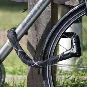 Ein Kettenschloss mit einem Schloss mit Schlüssel angekettet an einen Fahrradhalter.